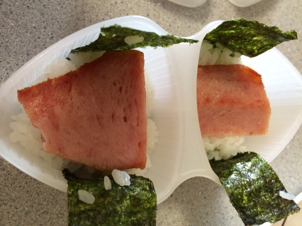 Fill halfway with rice, add odd pieces of spam or triangular cut spam into mold, top again with rice.
